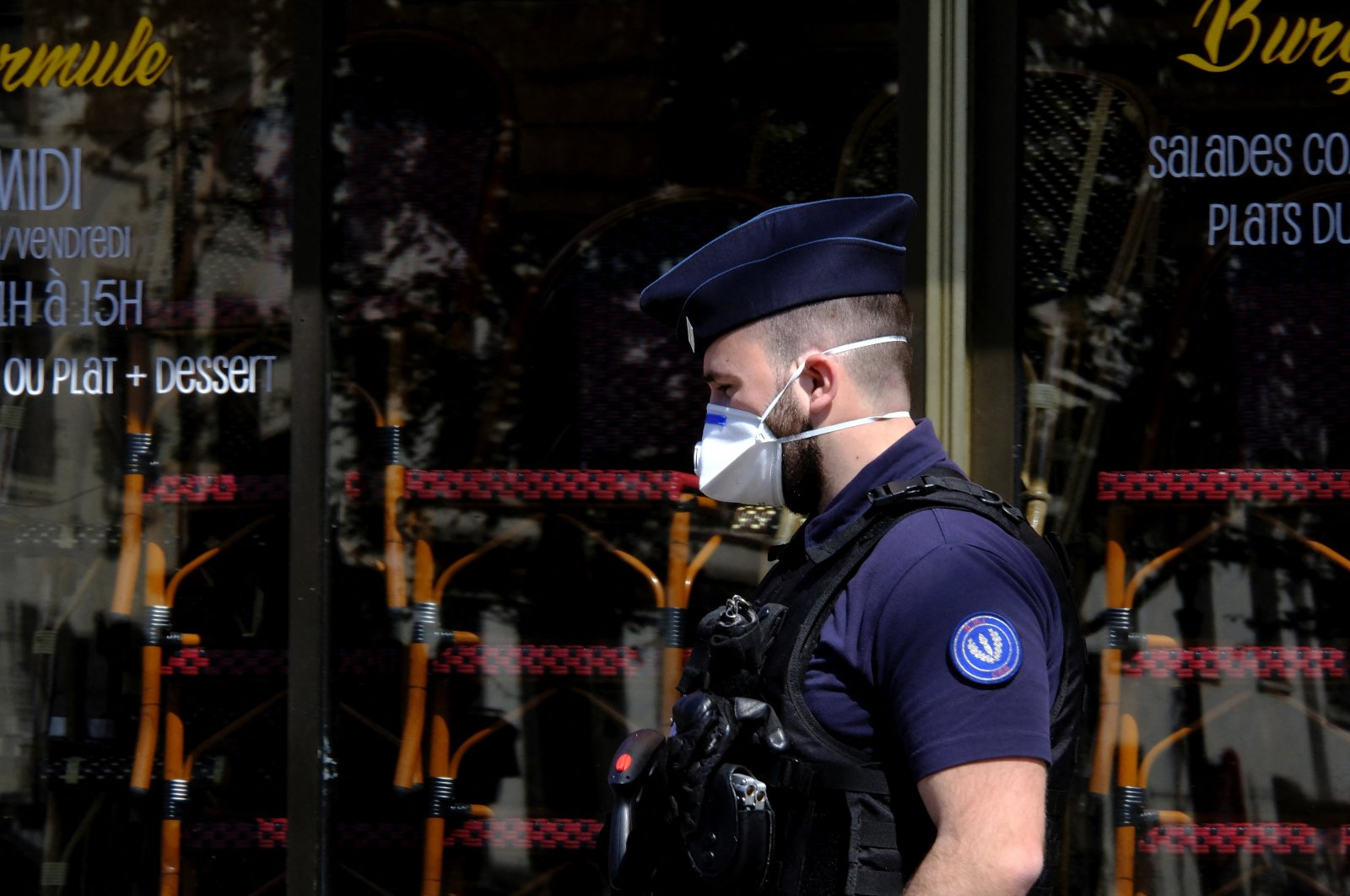 A French police officer wearing a protective face mask against the coronavirus walks in Paris, France, April 22, 2020. (Photo by Alfred Yaghobzadeh/acabapress.com via Reuters)