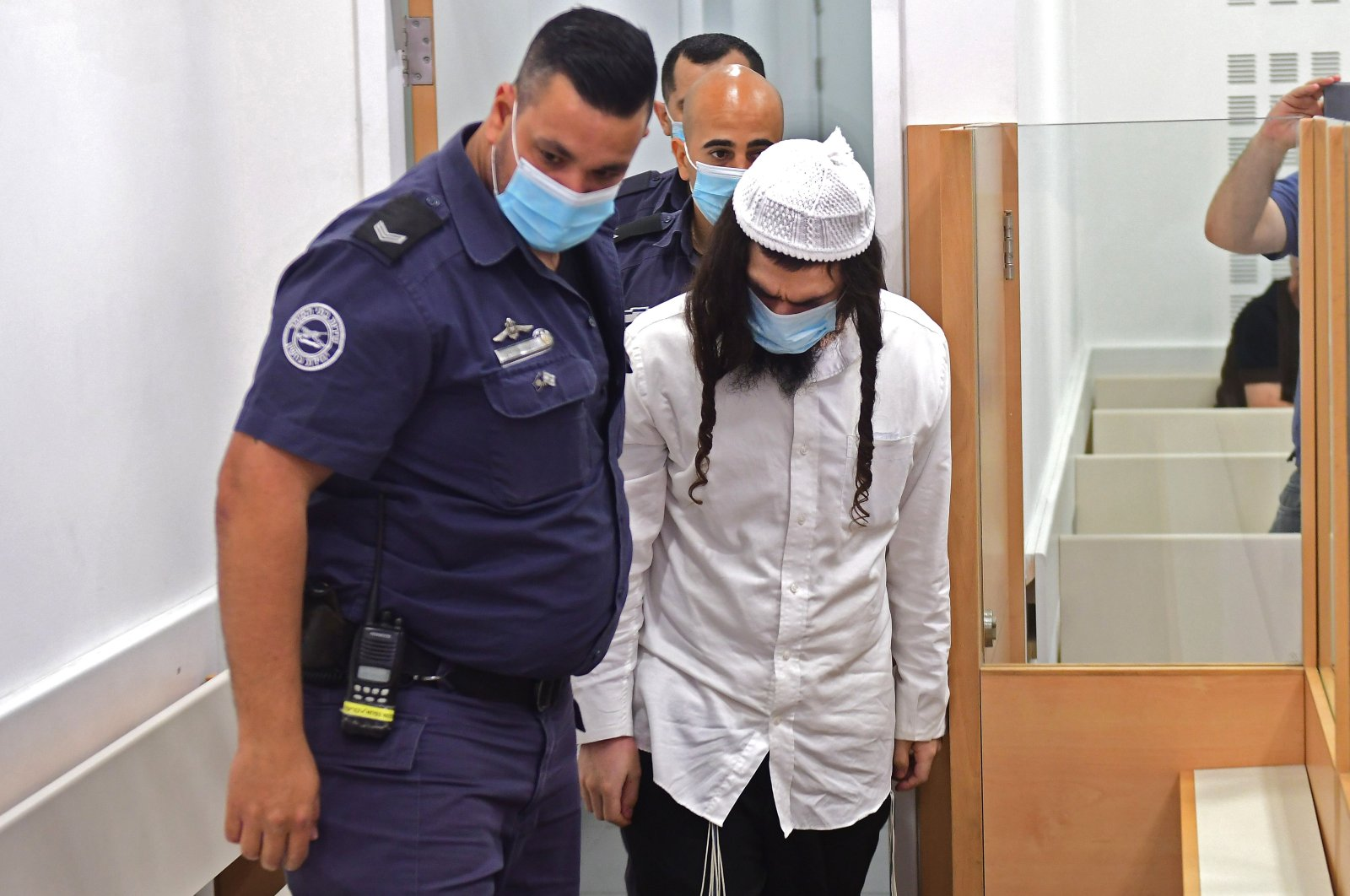 Amiram Ben-Uliel, a Jewish settler, is lead by police into court at the Central Lod District Court, in the central Israeli city on May 18, 2020, for his sentencing hearing over the 2015 arson attack that killed a Palestinian toddler and his parents. (AFP Photo)