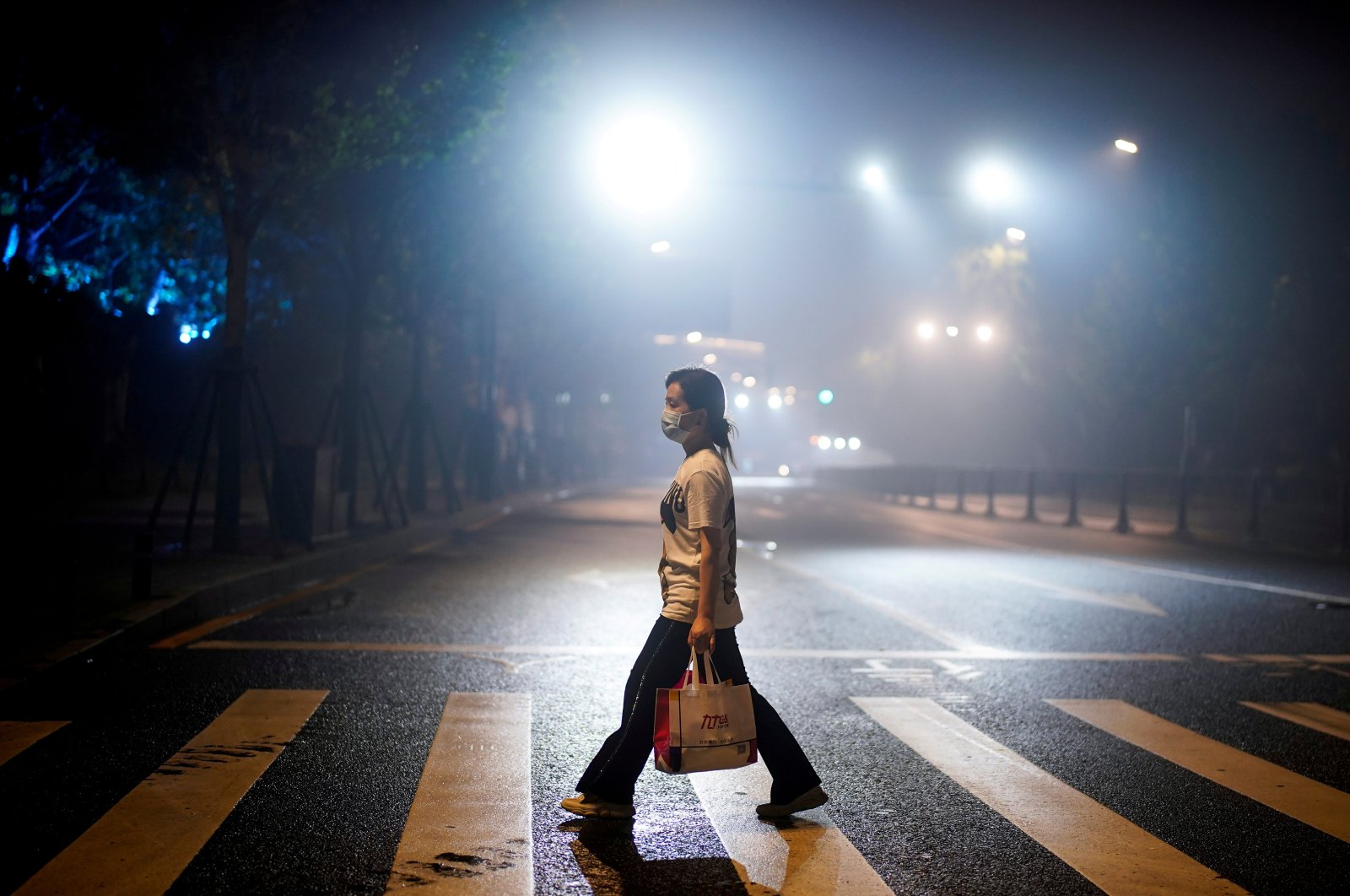 A woman wearing a protective mask walks on a street in Wuhan, the Chinese city where coronavirus originated, Hubei province, China, May 14, 2020. (Reuters Photo)