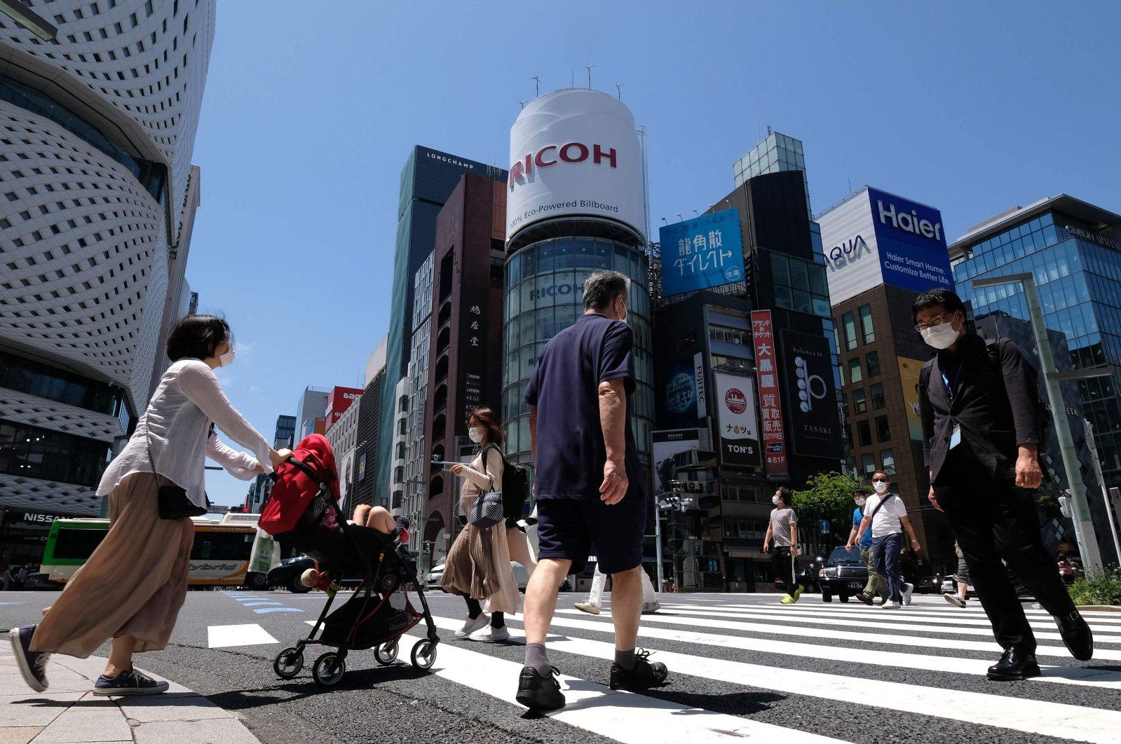 People wearing face masks amid concerns over the spread of the COVID-19 coronavirus cross a street in the Ginza shopping district in Tokyo, May 17, 2020. (AFP Photo)
