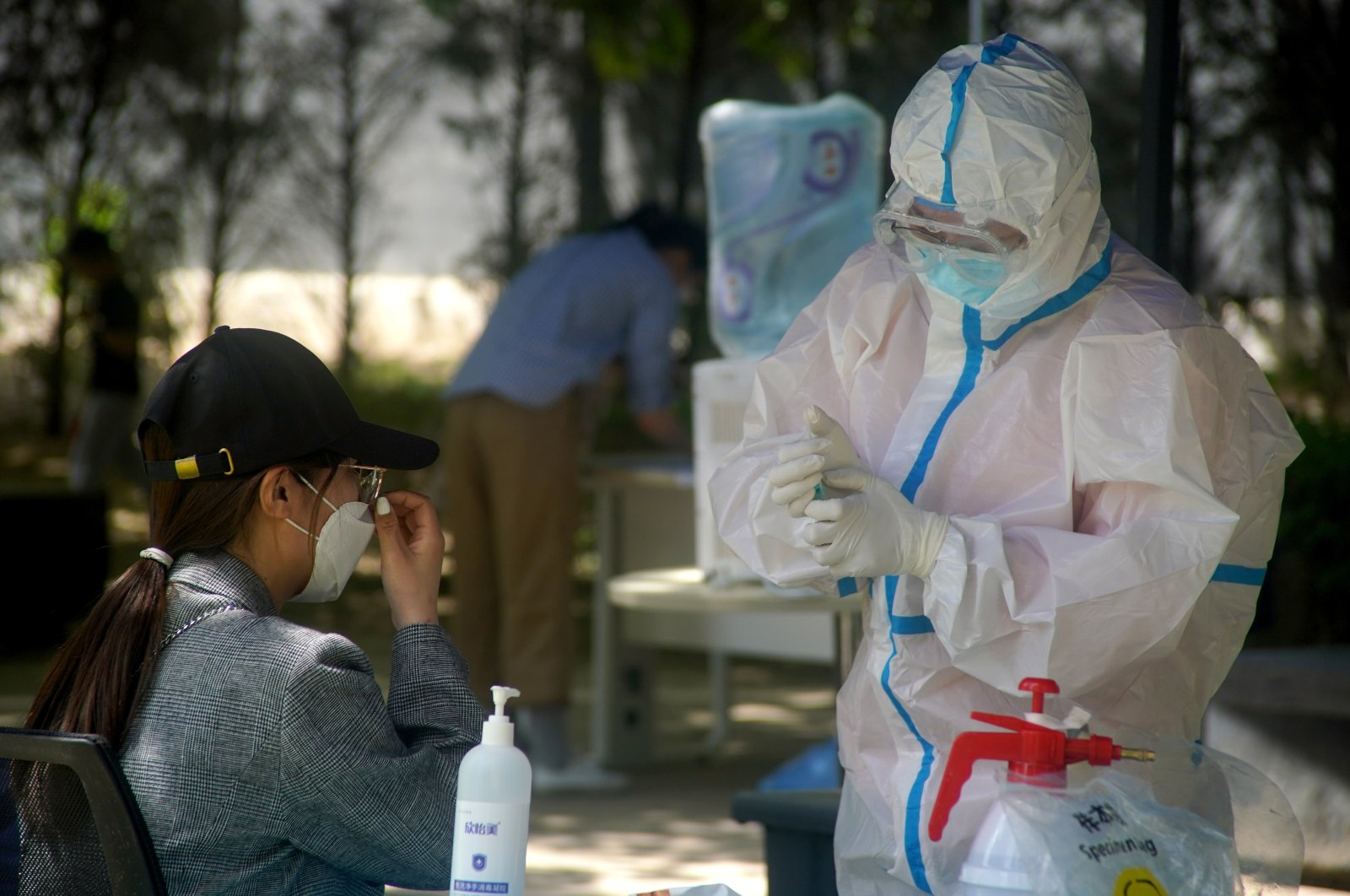 A medical worker wearing protective suit collects the sample after conducting nucleic acid testings for a woman, Beijing, May 18, 2020. (EPA Photo)
