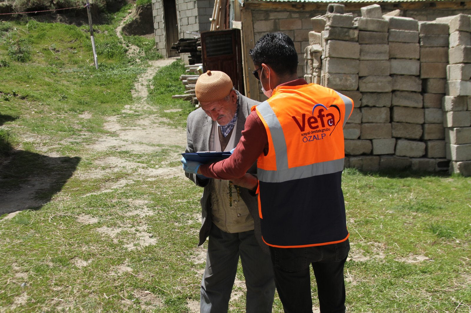 A Vefa Social Support Group volunteer distributes aid to an old man, Van, May 18, 2020. (AA)