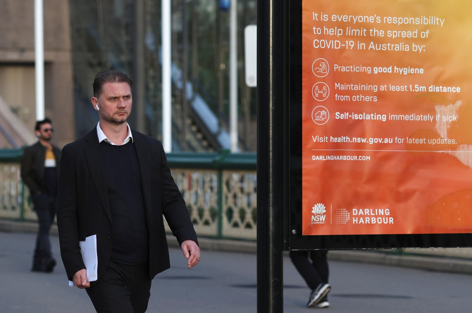 A man walks near an information board following the easing of restrictions implemented to curb the spread of the coronavirus, at Darling Harbour near the city center in Sydney, Australia, May 18, 2020. (Reuters Photo)