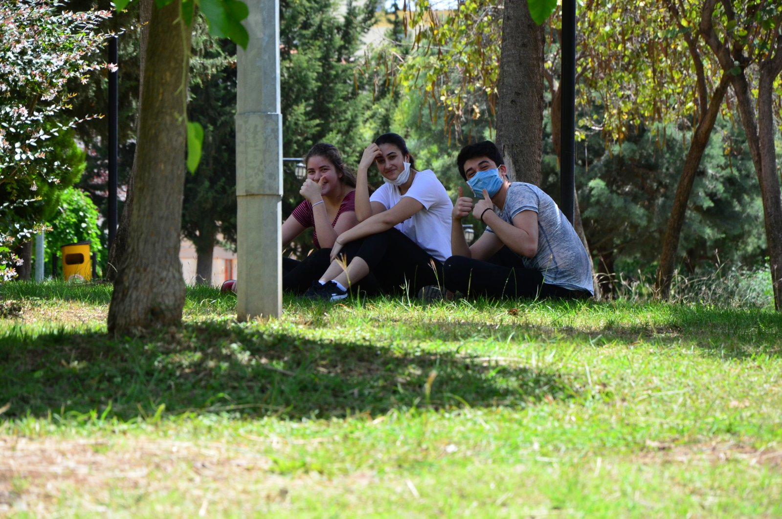 Three teenagers wearing masks sit in a park during the relaxation of the curfew for people under 20, in Adana, Turkey, May 15, 2020. (DHA Photo)