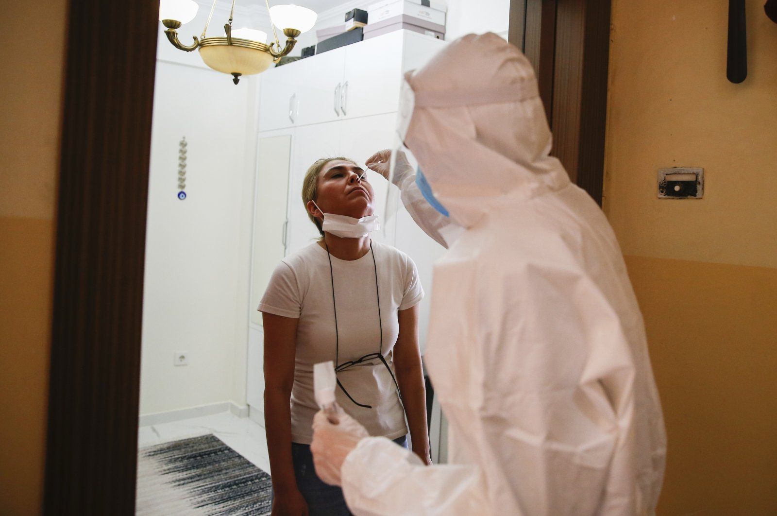 In this Friday, May 15, 2020 photo, a contact tracer with Turkey's Health Ministry's coronavirus contact tracing team, clad in white protective gear, mask and face shield, swabs Betul Sahbas, 47, left, who had been experiencing COVID-19 symptoms, to take a sample at her home in Istanbul. (AP Photo)