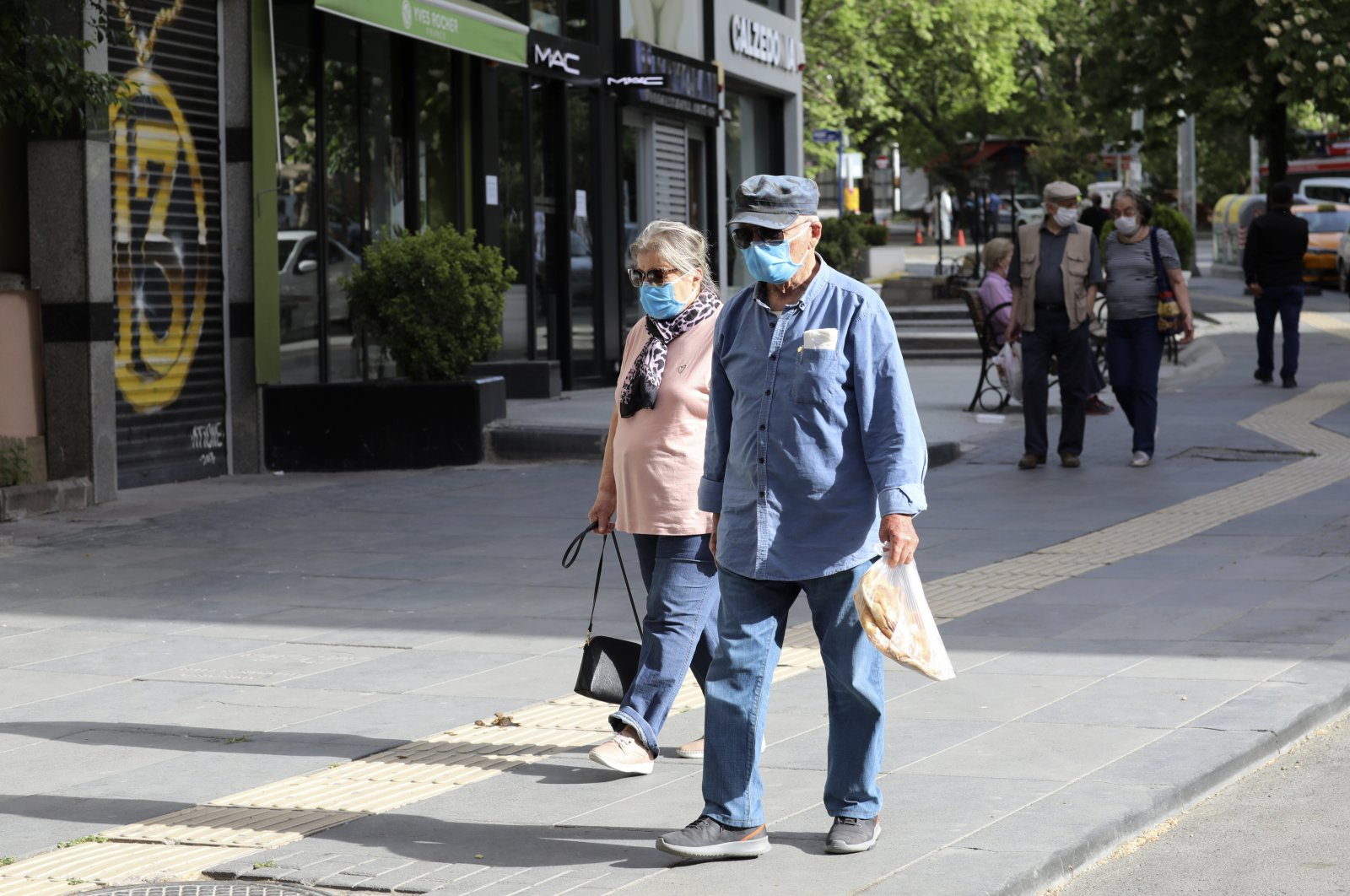 People wearing face masks for protection against coronavirus, walk in popular Tunali Hilmi Street during a four-day curfew declared by the government in an attempt to control the spread of coronavirus, in Ankara, Turkey, Sunday, May 17, 2020. (AP Photo)