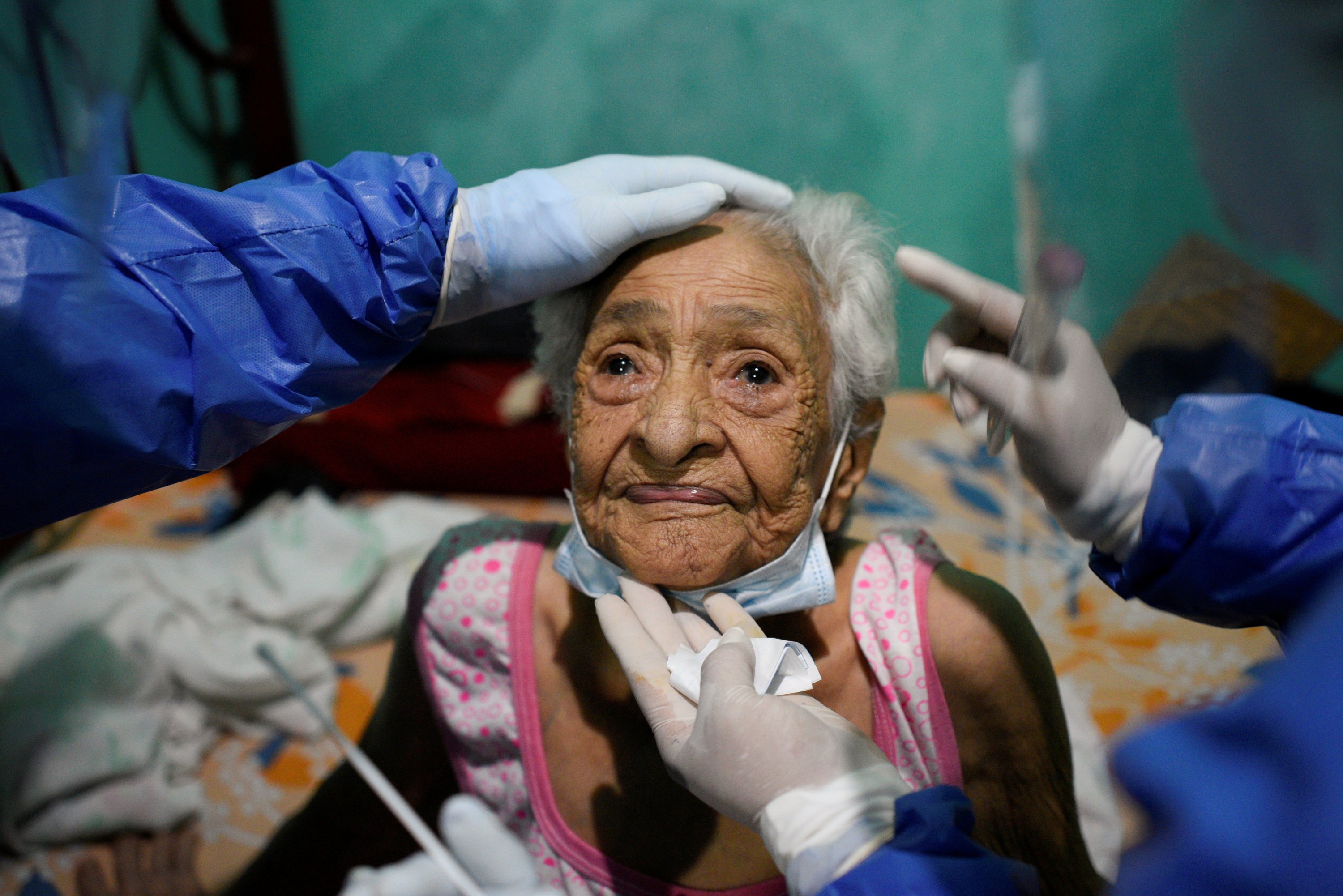 A 94-year-old woman prepares to have a sample taken by doctors from the Ecuadorian health ministry's rapid response team at her home in Guayaquil, Ecuador, April 29, 2020. (Reuters Photo)