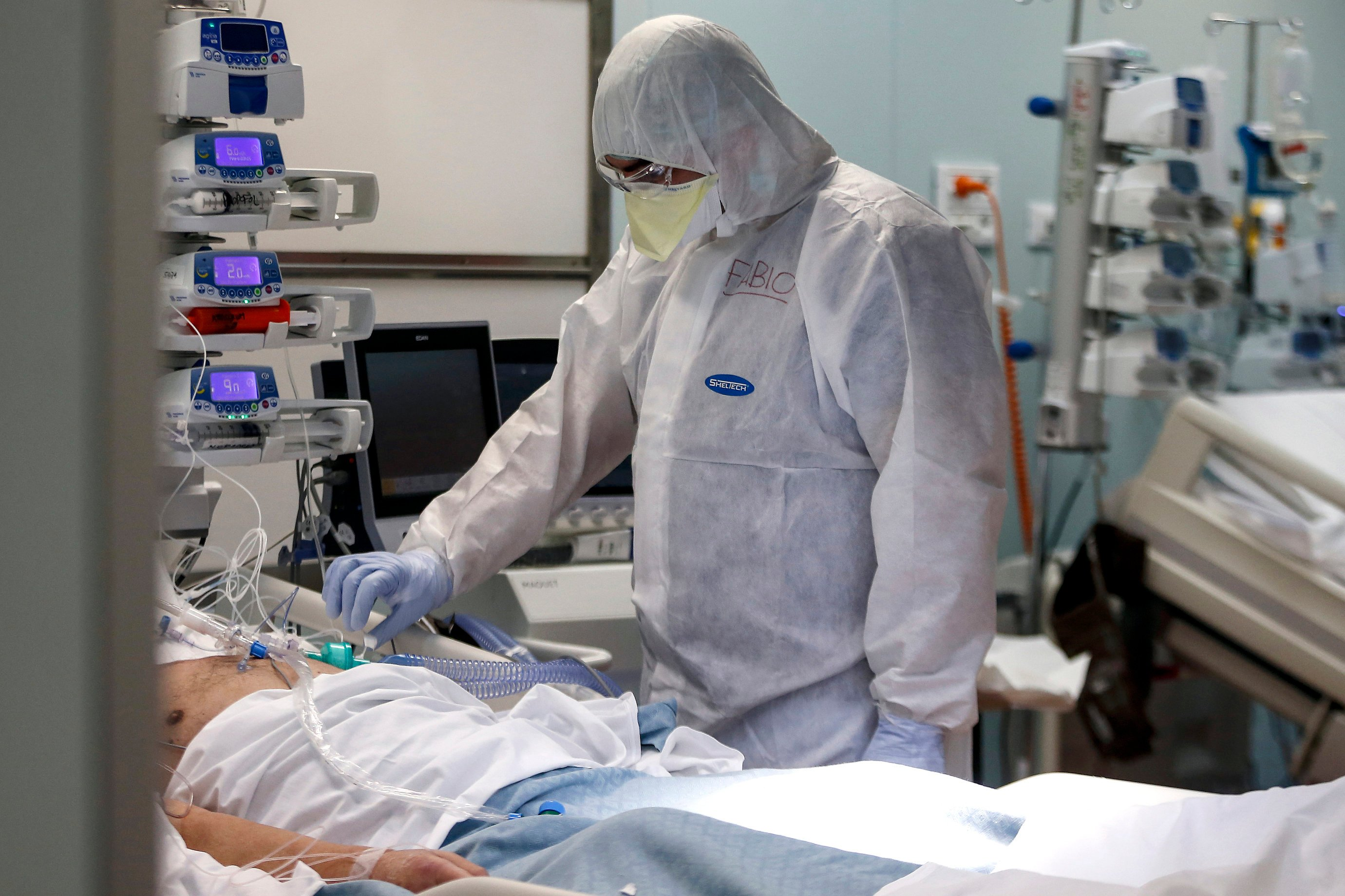 A medical staffer tends to a patient in the ICU unit of the COVID-19 hospital in Casalpalocco, near Rome, April 11, 2020. (AP Photo)