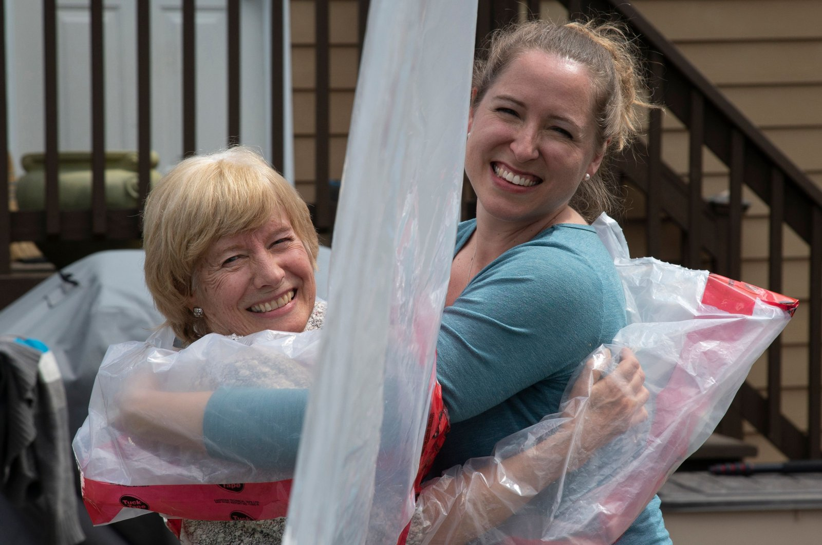 "Carolyn Ellis (R) hugs her mother Susan Watts using the ""Hug Glove"" that they created as a Mother's Day gift in Guelph, Ontario, Canada, May 16, 2020. (AFP Photo)"