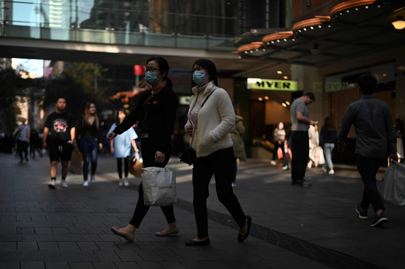 People wearing face masks walk through a shopping district in central Sydney on May 19, 2020. (AFP Photo)