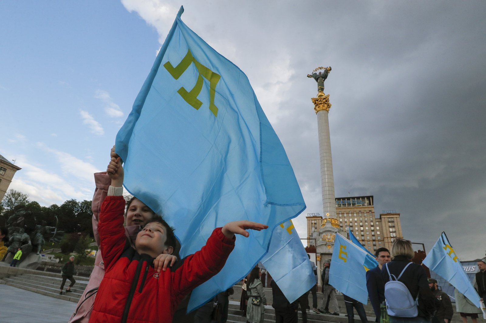 Crimean Tatars hold flags during a commemoration meeting on Independence Square in Kyiv, Ukraine, May 18, 2020. (EPA Photo)