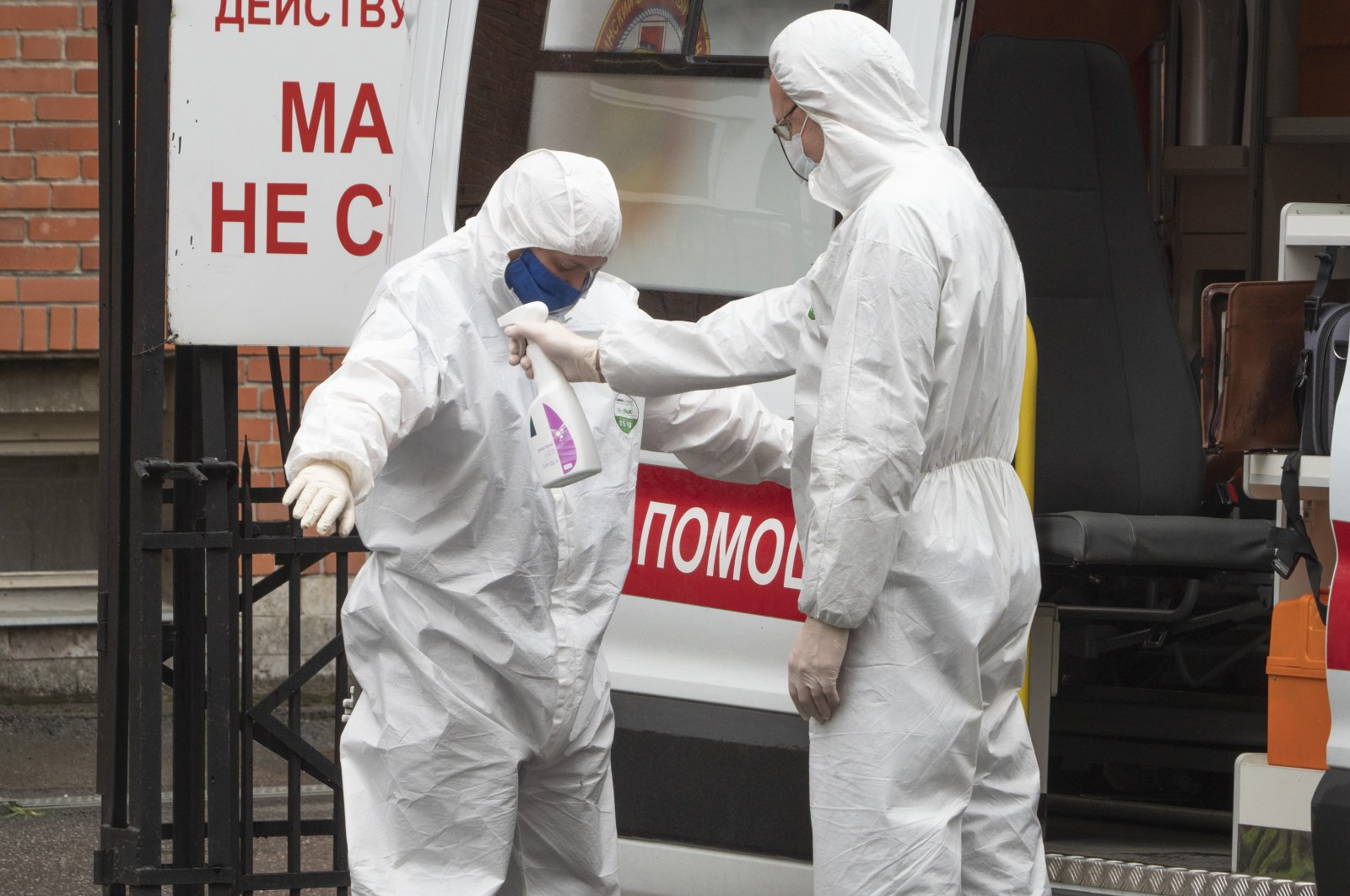 A medical worker wearing protective equipment disinfects his colleague after escorting a patient by ambulance to a hospital for COVID-19 patients in St. Petersburg, Russia, May 18, 2020. (AP Photo)