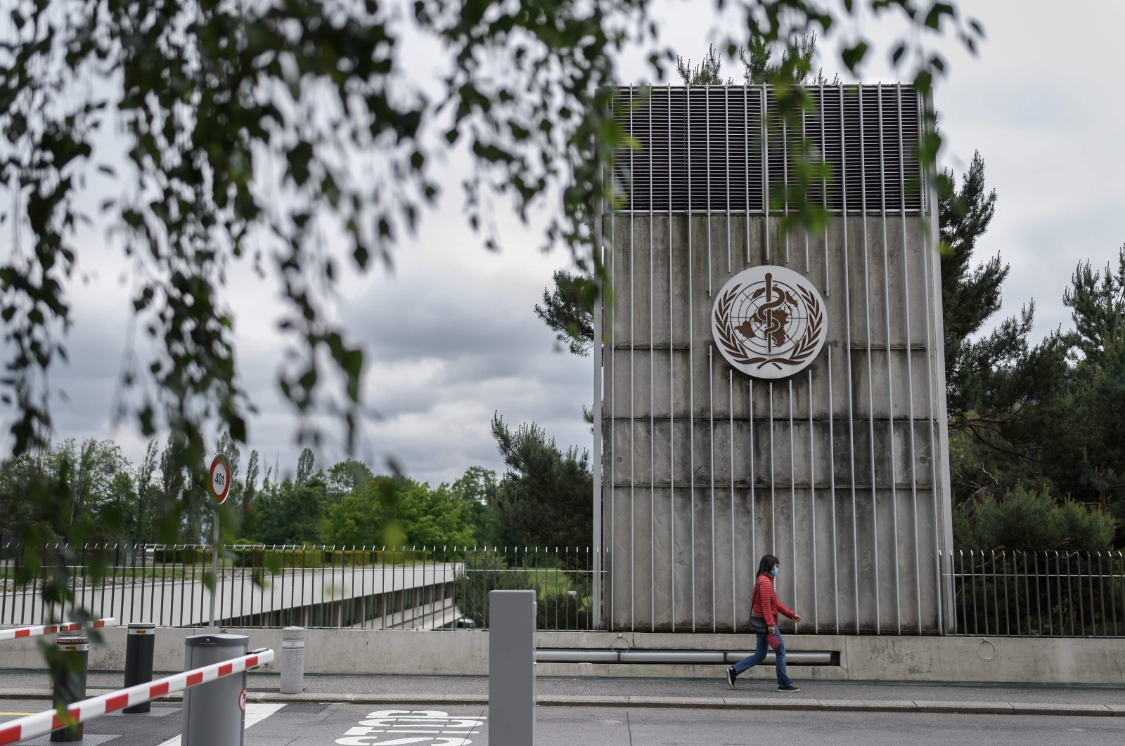 A woman wearing a protective facemask walks underneath a sign of the World Health Organization (WHO) in Geneva next to their headquarters, May 12, 2020. (AFP Photo)