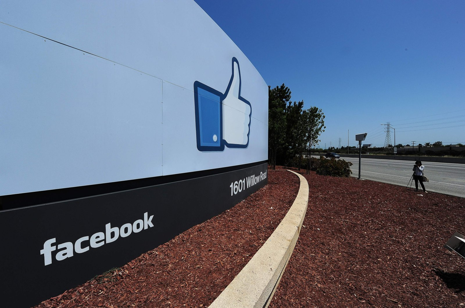 A woman shoots video of the sign at the entrance to the Facebook main campus in Menlo Park, California, U.S., May 15, 2012. (AFP Photo)