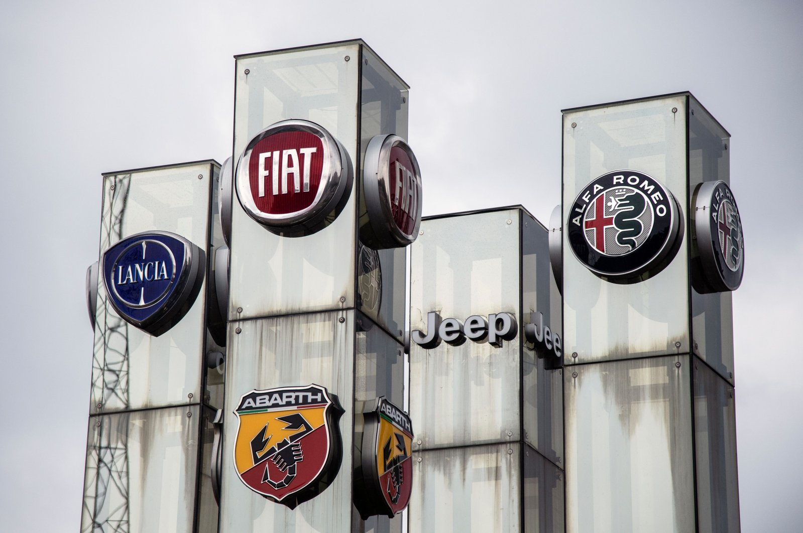 The logos of Lancia, Fiat, Abarth Jeep and Alfa Romeo automakers, brands of Fiat Chrysler Automobiles (FCA) company, Turin, Italy, May 27, 2019. (AFP Photo)