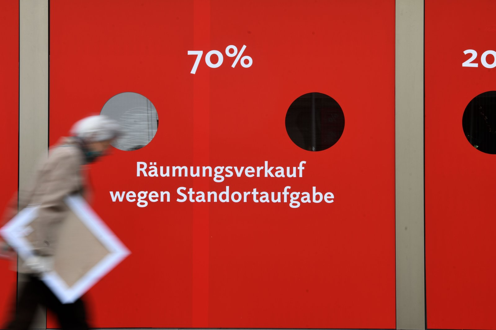 A woman walks past a sign for a clearance sale at a shop in Essen, western Germany on May 12, 2020. (AFP Photo)