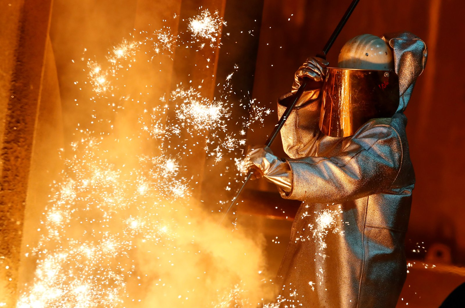 A steel worker of ThyssenKrupp stands amid sparks of raw iron coming from a blast furnace at a ThyssenKrupp steel factory in Duisburg, western Germany, Jan. 30, 2020. (Reuters Photo)