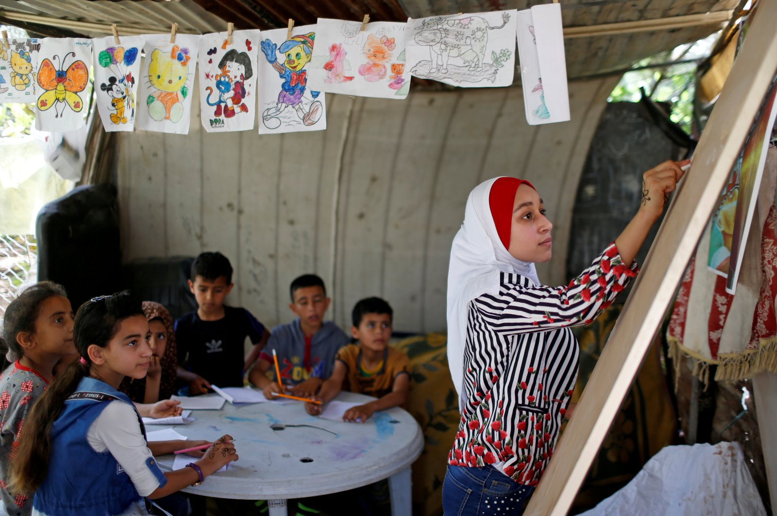 A Palestinian schoolgirl Fajr Hmaid, 13, holds Arabic language lessons for her neighbors' children as schools are shut due to the coronavirus restrictions, at her family house, Gaza, May 19, 2020.