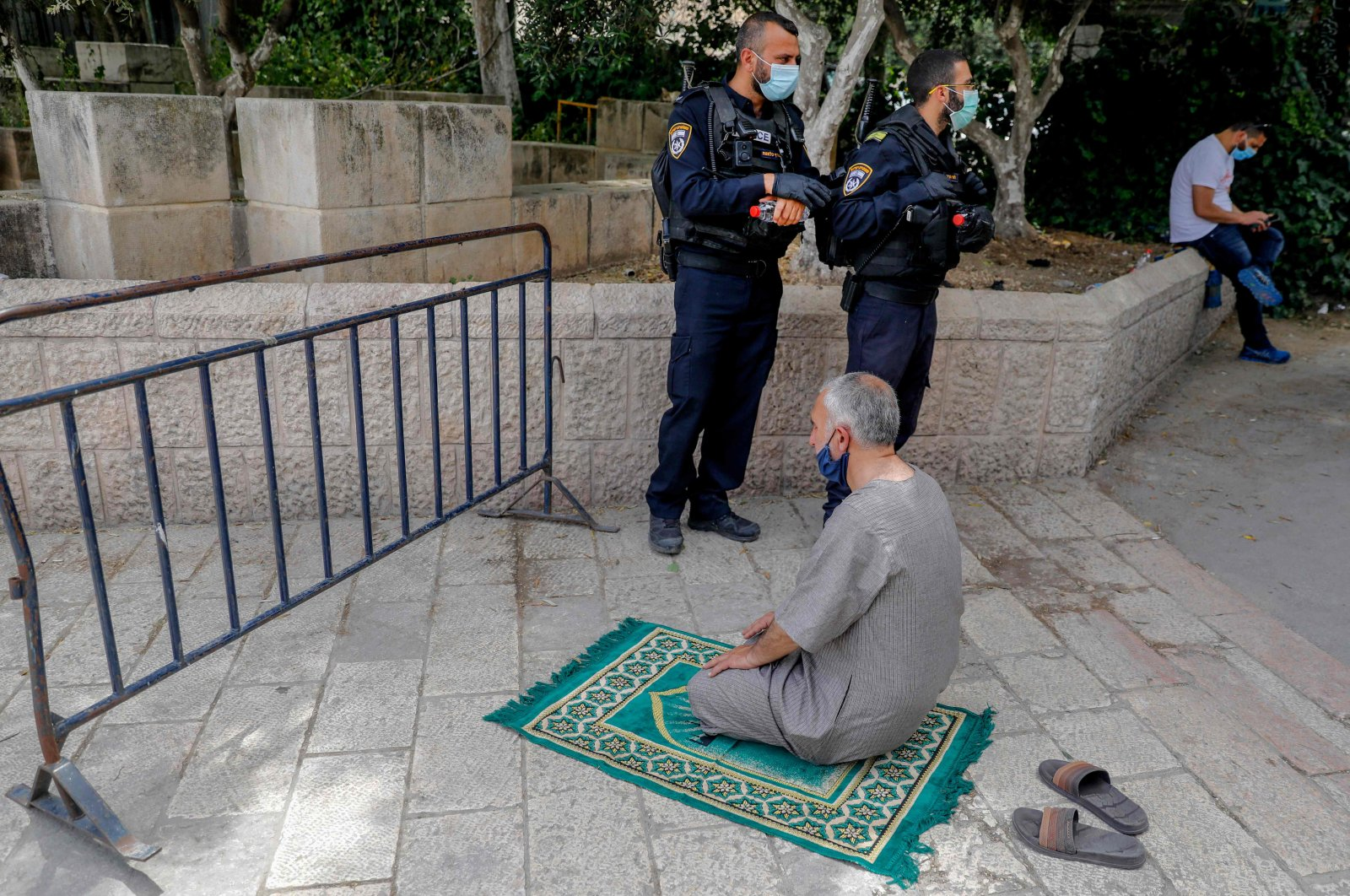Israeli security forces look on as a Palestinian worshipper performs the Friday prayer during the Muslim holy month of Ramadan, outside the closed Al-Aqsa mosque compound in the Old City of Jerusalem, May 15, 2020. (AFP Photo)
