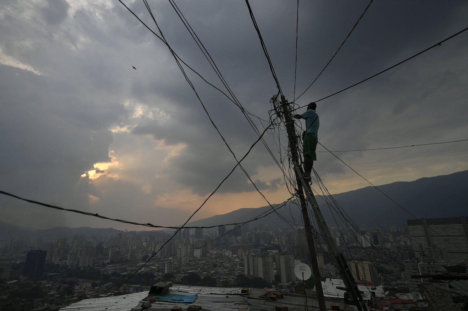 A man fixes power lines in the San Agustin neighborhood of Caracas, Venezuela,  May 17, 2020. (AP Photo)