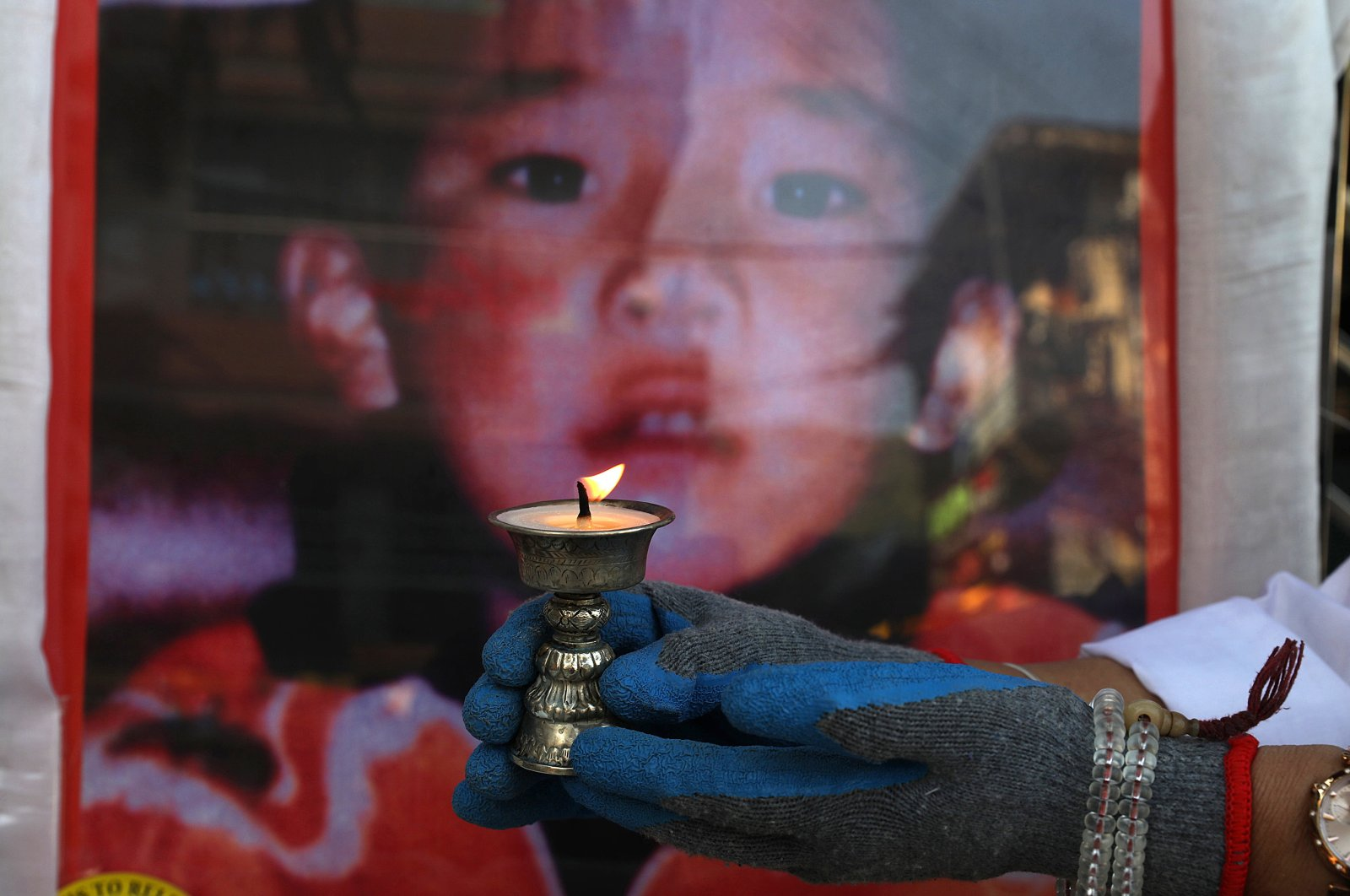 A Tibetan woman living in exile and a member of the Tibetan Women's Association lights a butter lamp during an event to mark the 31st birthday of Panchen Lama in McLeod Ganj, near Dharamsala, India, April 25, 2020.(EPA Photo)