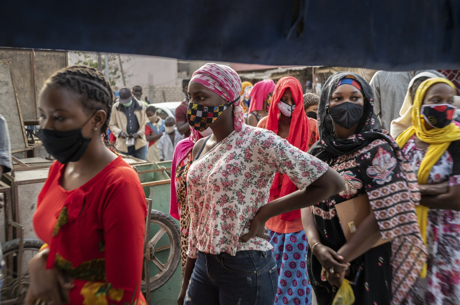 Women wear face masks as they queue to buy bread on the first day of the Muslim fasting month of Ramadan, in Dakar, Senegal, April 25, 2020. (AP Photo)