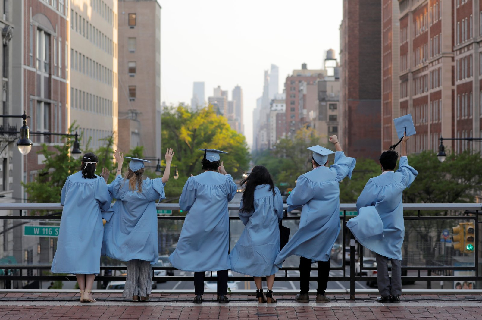 Master's students from the Columbia University Graduate School of Architecture, Planning and Preservation (GSAPP) wave to passing traffic from an overpass the day before their graduation ceremony, which is to be held online due to the outbreak of the coronavirus disease in Manhattan, New York City, U.S., May 15, 2020. (Reuters Photo)
