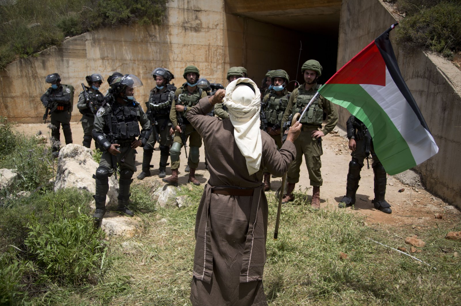 """A Palestinian holds the national flag in front of Israeli border police during a protest marking the 72nd anniversary """"Nakba,"""" or catastrophe – a leading symbol against the Israeli annexations and occupations, near the West Bank city of Nablus, May 15, 2020. (AP Photo)"""