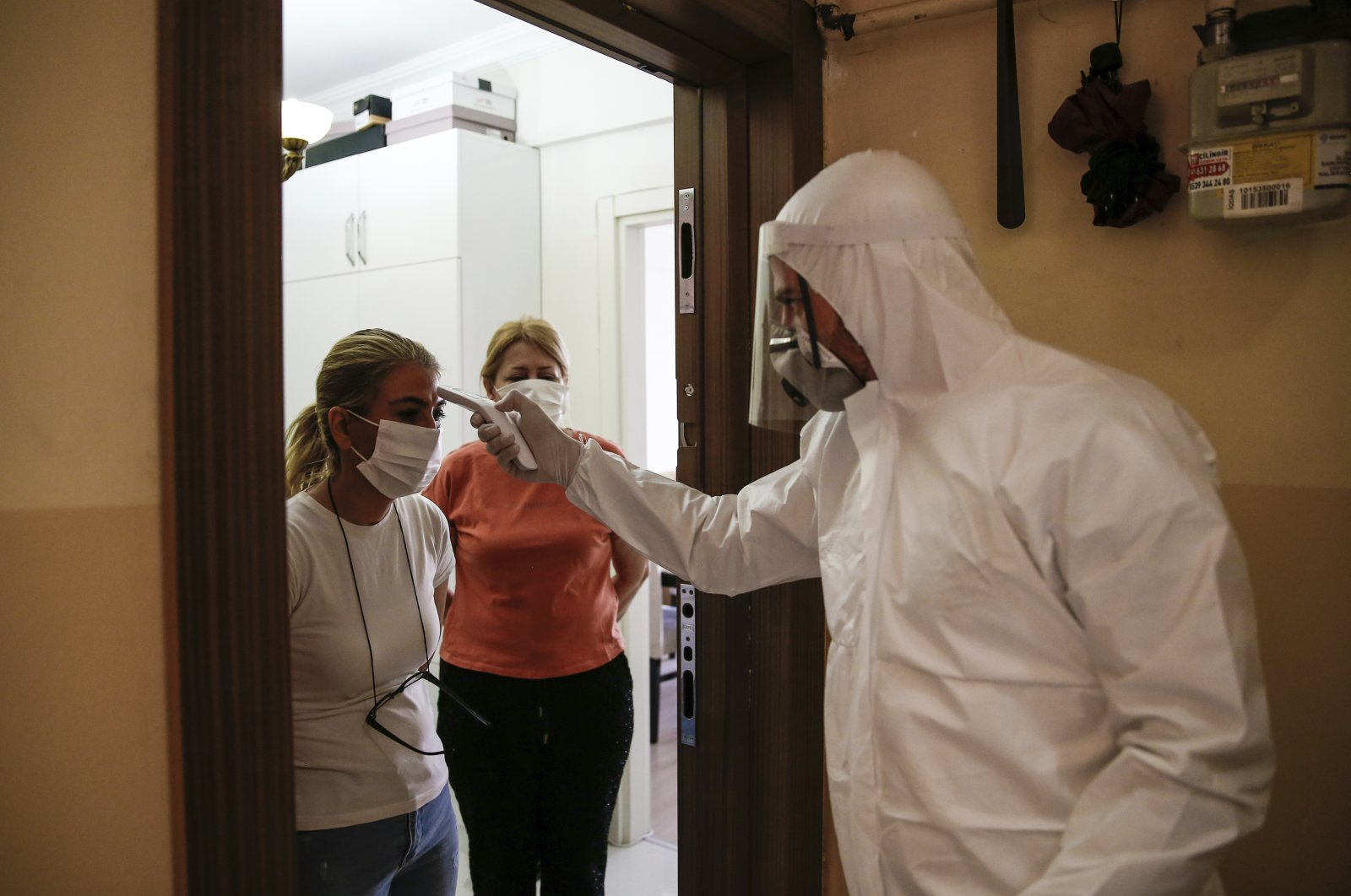 A contact tracer takes the temperature of Betül Şahbaz (L) who had been experiencing COVID-19 symptoms, in Istanbul, Turkey, May 15, 2020. (AP Photo)