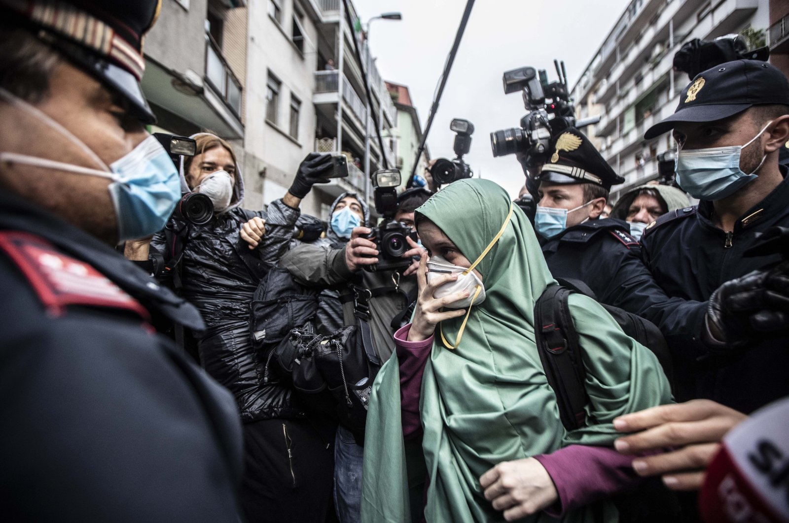 Silvia Romano, escorted by Carabinieri officers, arrives at her home wearing a green garment typical of Somali Muslim women and a surgical mask to guard against COVID-19, in Milan, Italy, May 11, 2020. (AP Photo)