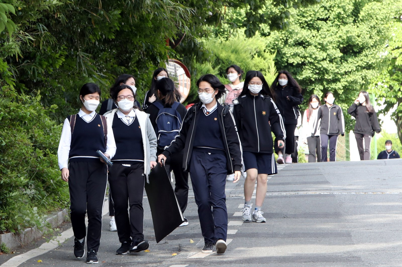 High school students wearing protective masks walk after finishing their classes, as schools reopen following the global outbreak of COVID-19, Gwangju, South Korea, May 20, 2020. (Yonhap via Reuters Photo)