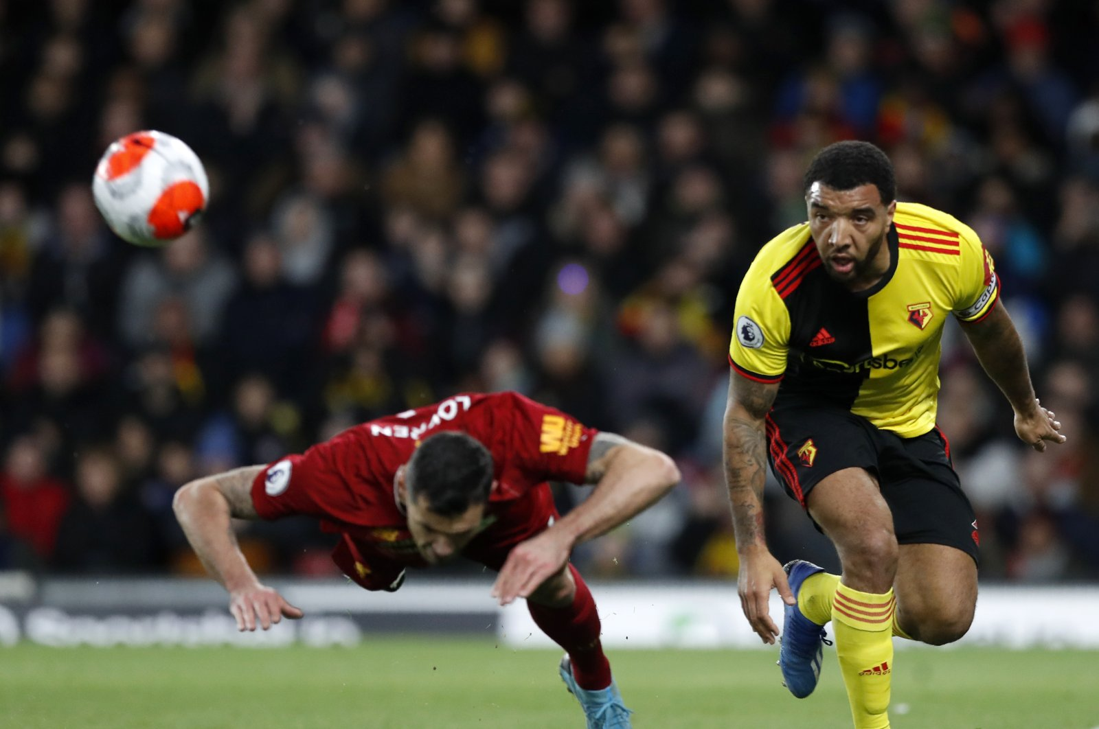 Watford's Troy Deeney (R) duels for the ball with Liverpool's Dejan Lovren during a Premier League match in Watford, England, Feb. 29, 2020. (AP Photo)