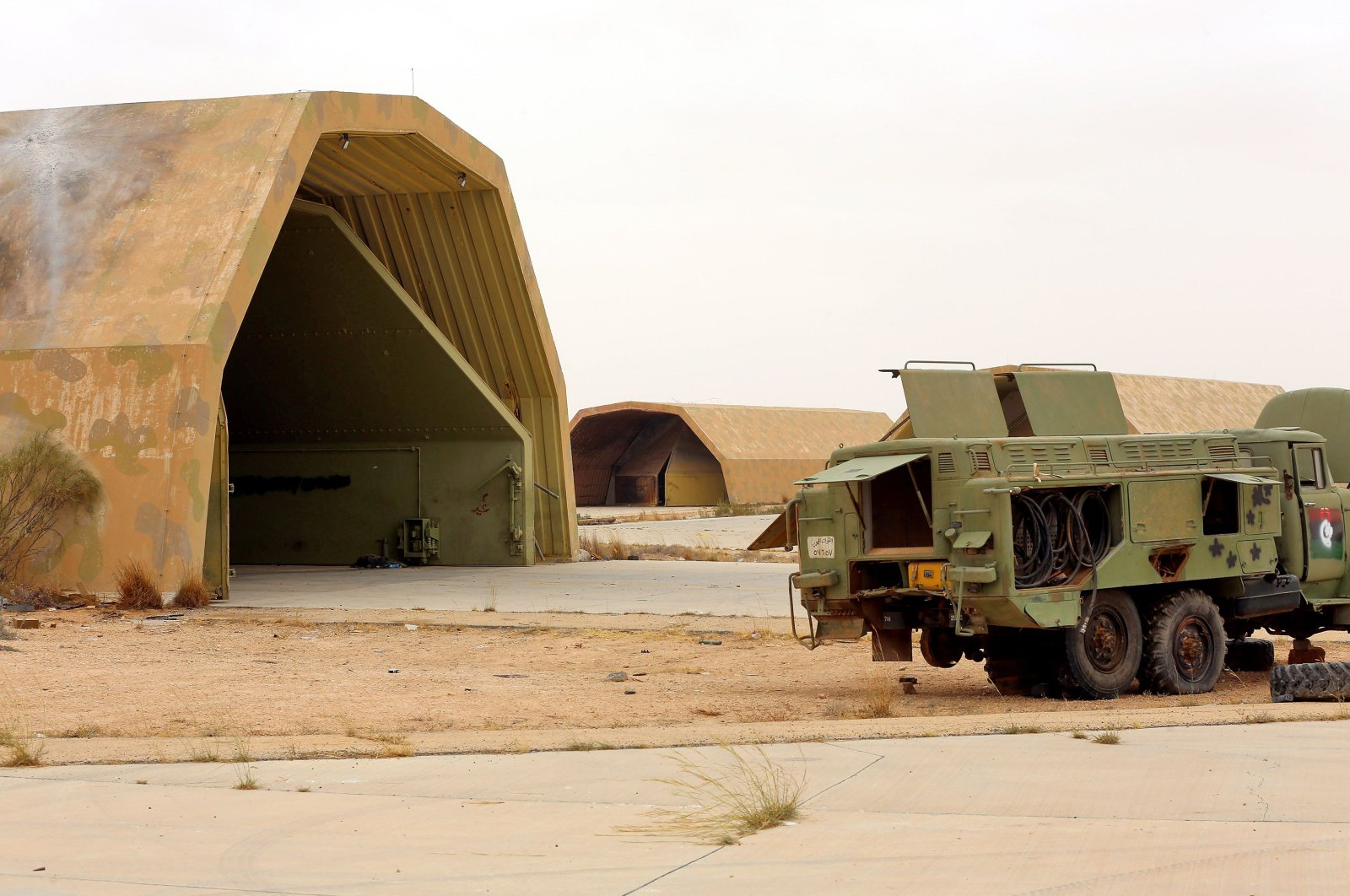 Vehicles are seen outside a hangar at al-Watiya air base, which was seized by forces loyal to Libya's U.N.-recognized Government of National Accord (GNA), southwest of the capital Tripoli, May 18, 2020. (AFP Photo)