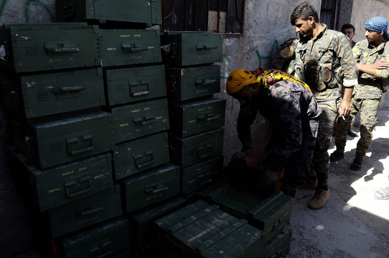 YPG terrorists unload boxes of ammunition, supplied by the US-led coalition, in a village north of Raqqa, June 7, 2017. (AFP)