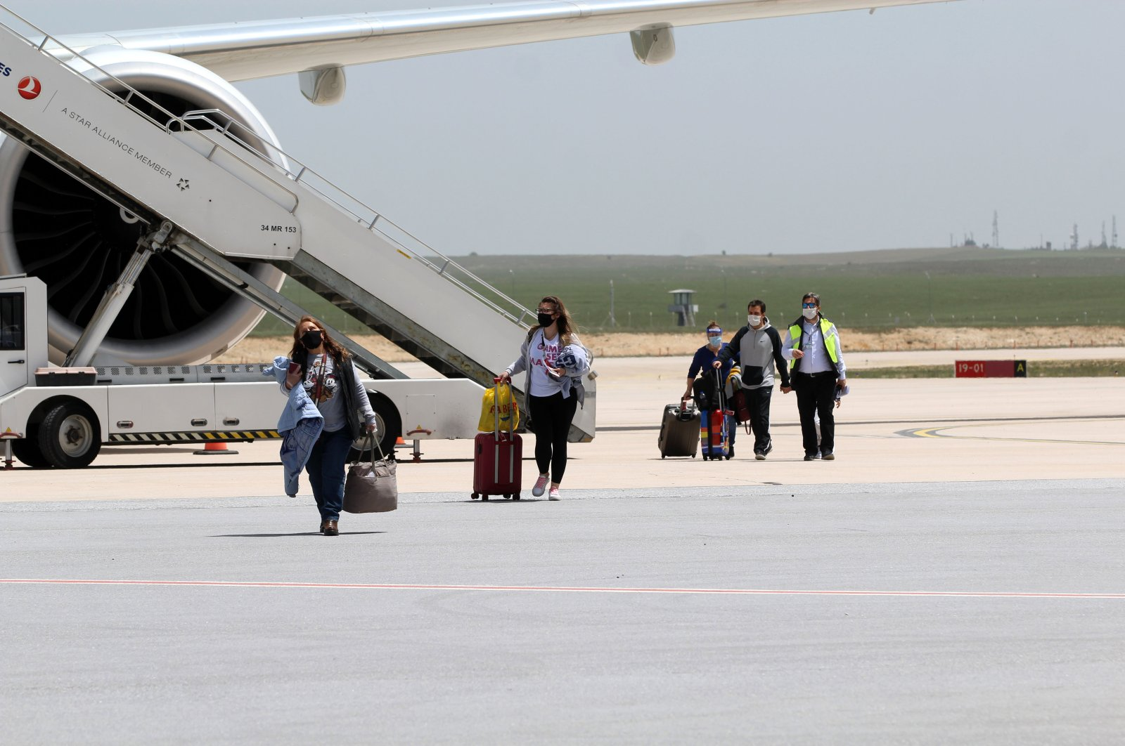 People wearing masks disembark a plane that arrived from the United States, in Sivas, Turkey, May 18, 2020. (AA Photo)