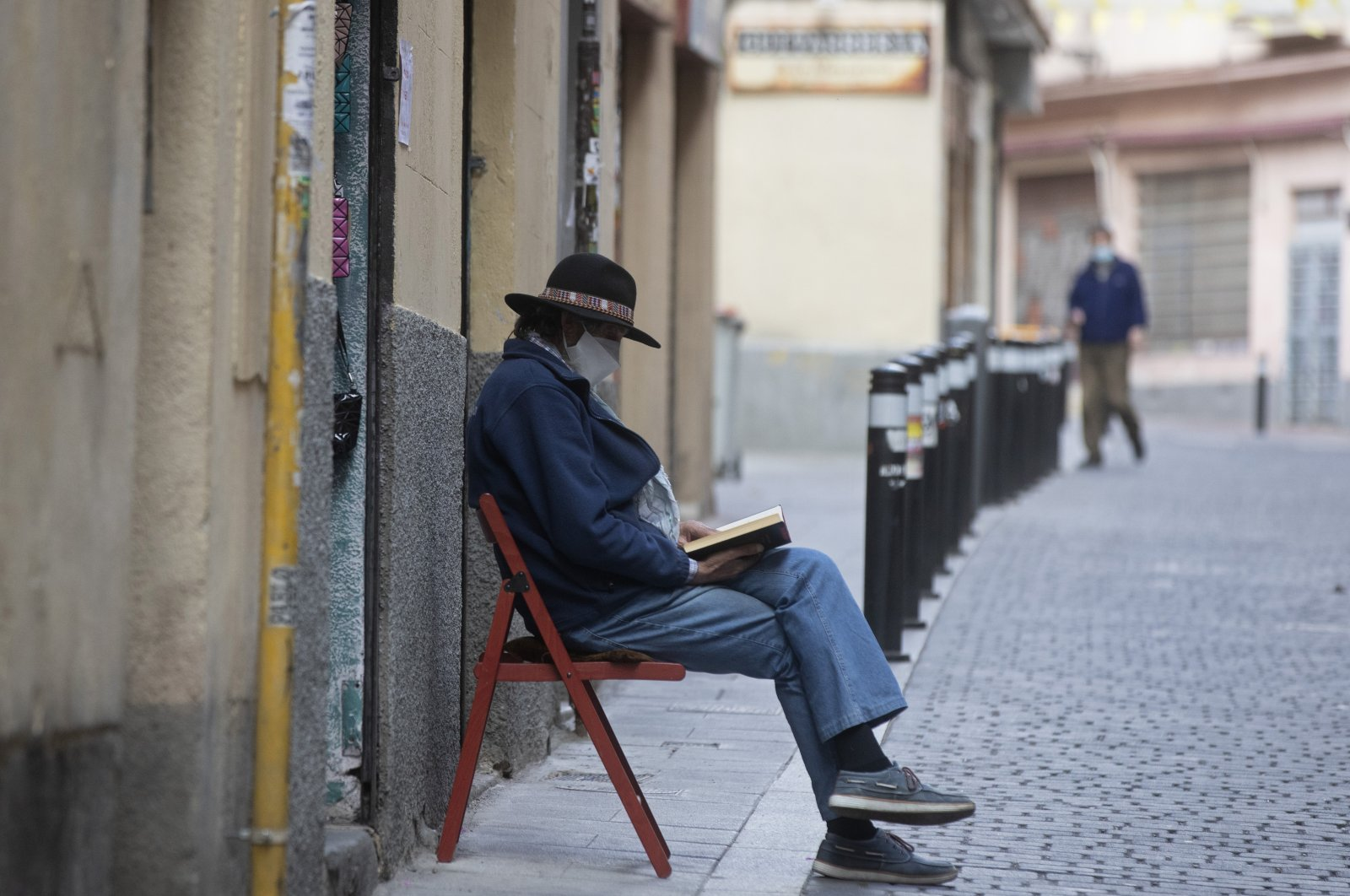 A man wearing a face mask to protect against coronavirus sits and waits for customers outside a small shop while reading a book, Madrid, Spain, May 16, 2020. (AP Photo)