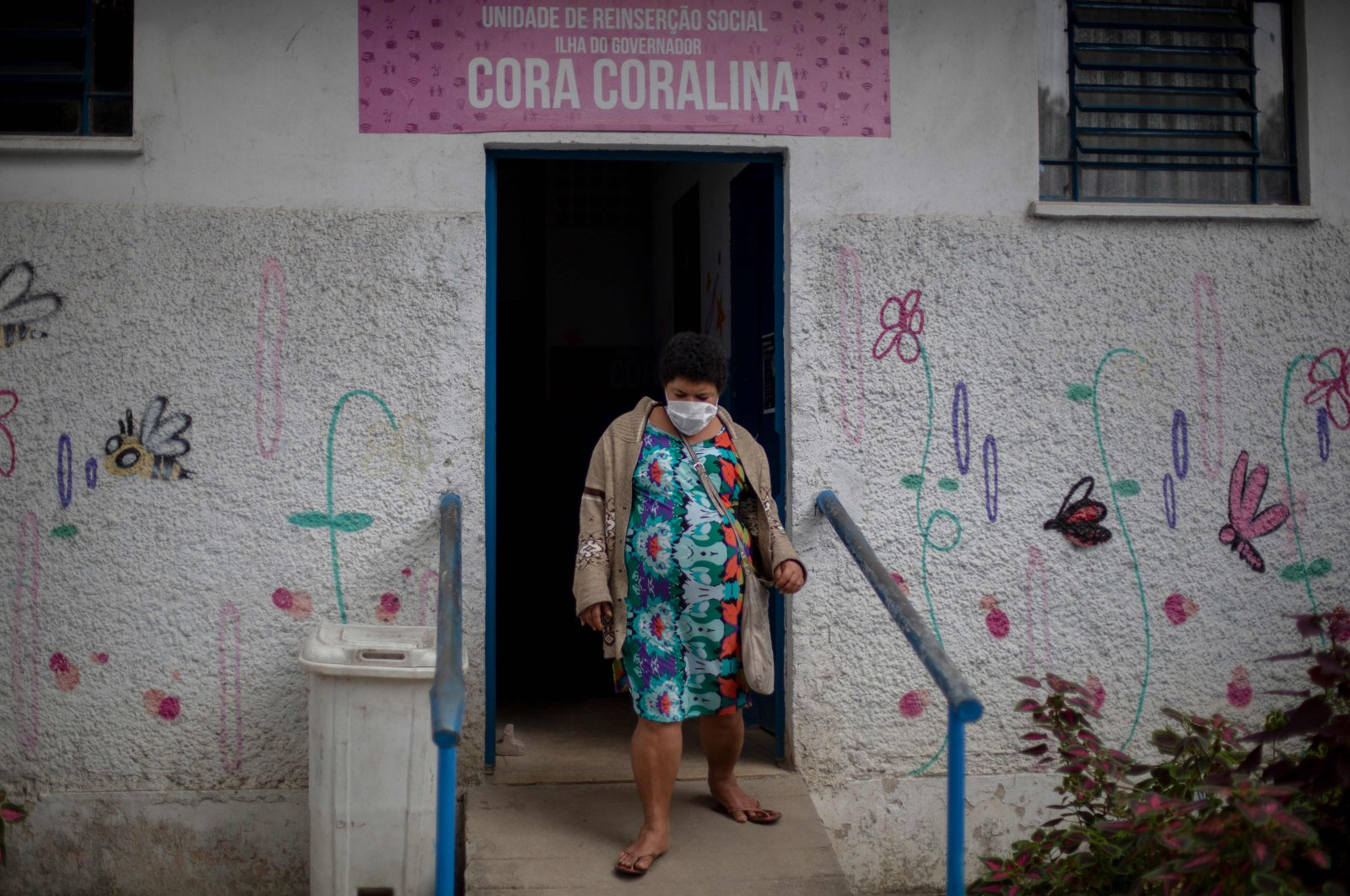 A resident of the public shelter goes out of a dormitory while Brazil's Armed Forces soldiers disinfect the place at the Ilha do Governador neighborhood, Rio de Janeiro, May 14, 2020. (AFP Photo)