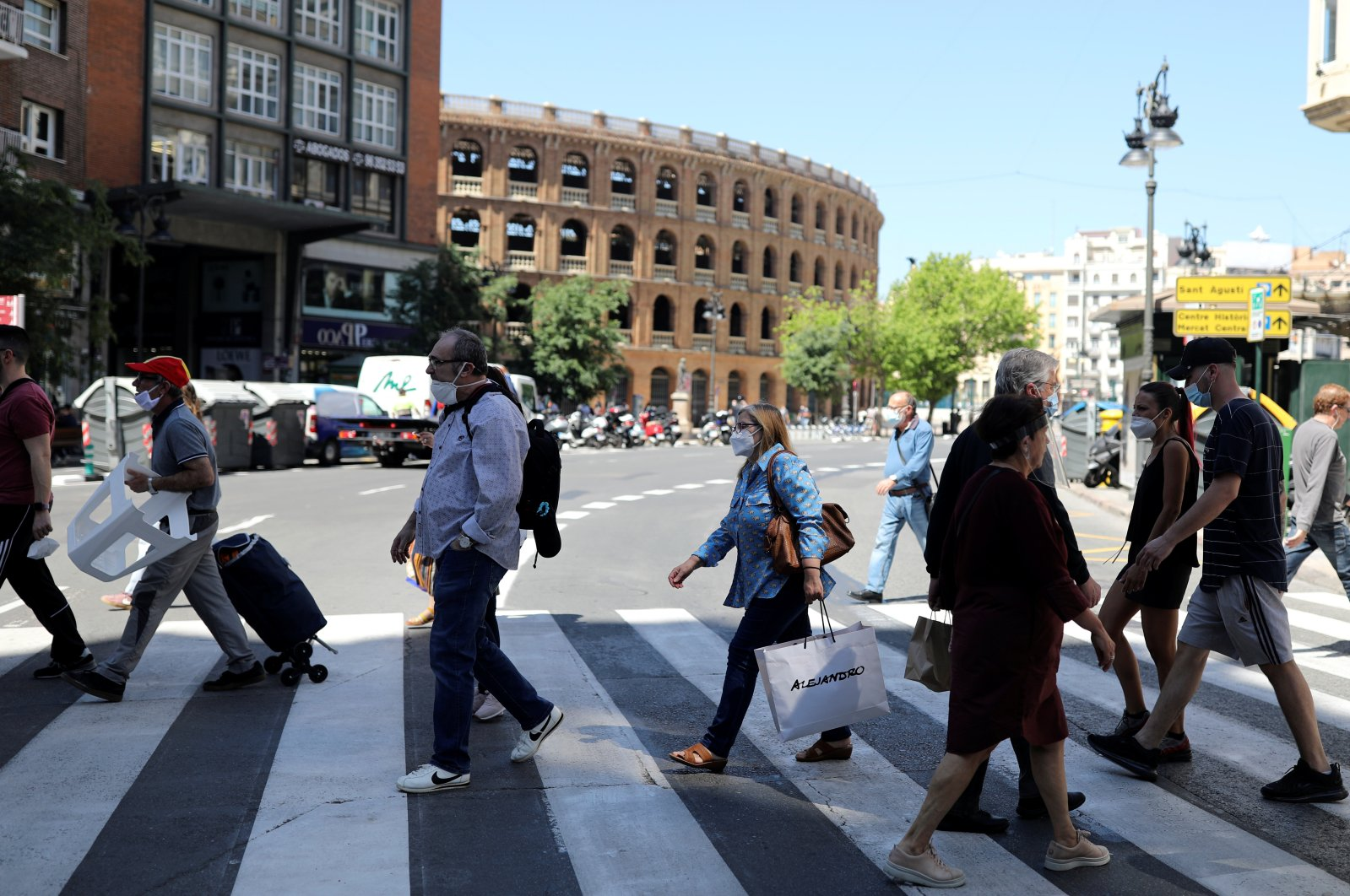 People wearing face masks walk on a crosswalk, as some Spanish provinces are allowed to ease lockdown restrictions during phase one, amid the coronavirus outbreak, in Valencia, Spain, May 19, 2020. (Reuters Photo)