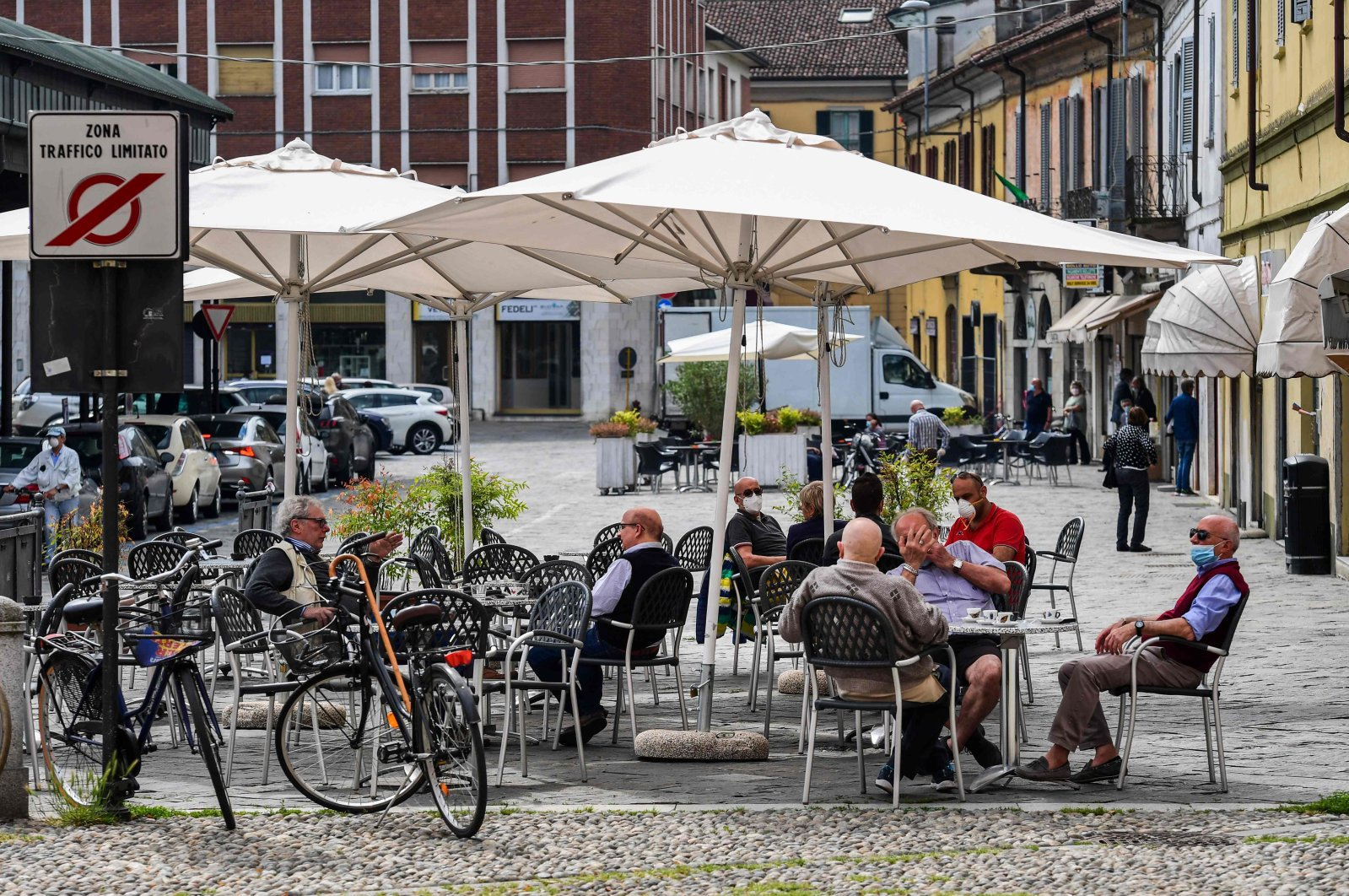 Residents have coffee and drinks at a terrace on May 20, 2020 in Codogno, southeast of Milan, as the country's is easing its lockdown aimed at curbing the spread of the COVID-19 infection. (AFP Photo)