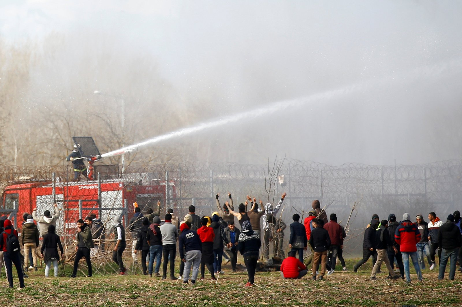 A Greek firefighter uses a water cannon as migrants gather on the Turkish-Greek border near Turkey's Pazarkule border crossing with Greece's Kastanies, in Edirne, Turkey, March 7, 2020. (Reuters File Photo)