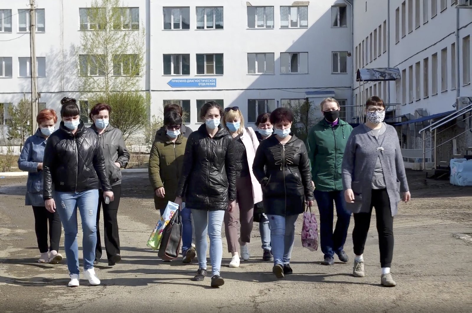 In this photo taken from video footage, nurses and orderlies walk to meet journalists in front of a hospital in Russia's Siberian city Chita, Russia, Saturday, May 16, 2020. (AP Photo)