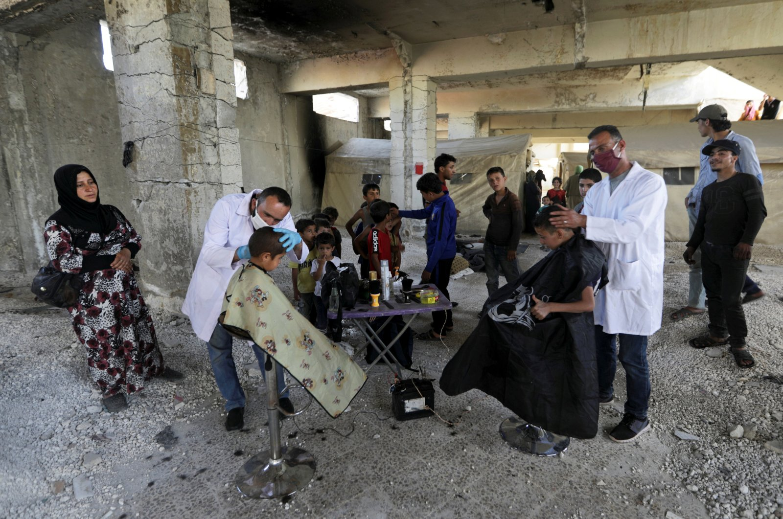 Volunteer hairdressers from the International Association for Relief and Development (ONSUR) wearing face masks and gloves cut the hair of internally displaced children at a camp for the displaced in Idlib, Syria, May 19, 2020. (Reuters Photo)