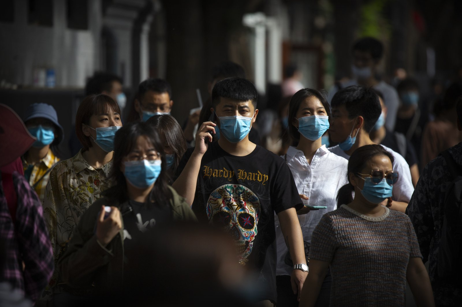 People wearing face masks to protect against the spread of the new coronavirus walk along a pedestrian shopping street in Beijing, China, May 16, 2020. (AP Photo)