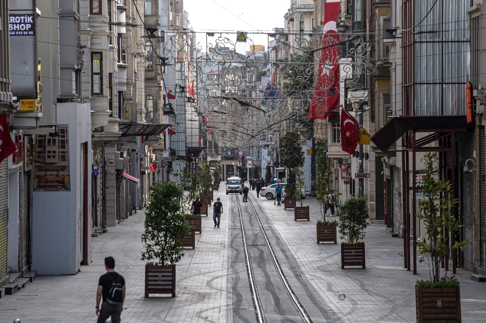 People walk along a deserted Istiklal Avenue in the Taksim district of Istanbul, Turkey, during a four-day curfew to prevent the spread of the COVID-19 pandemic, May 16, 2020. (AFP Photo)