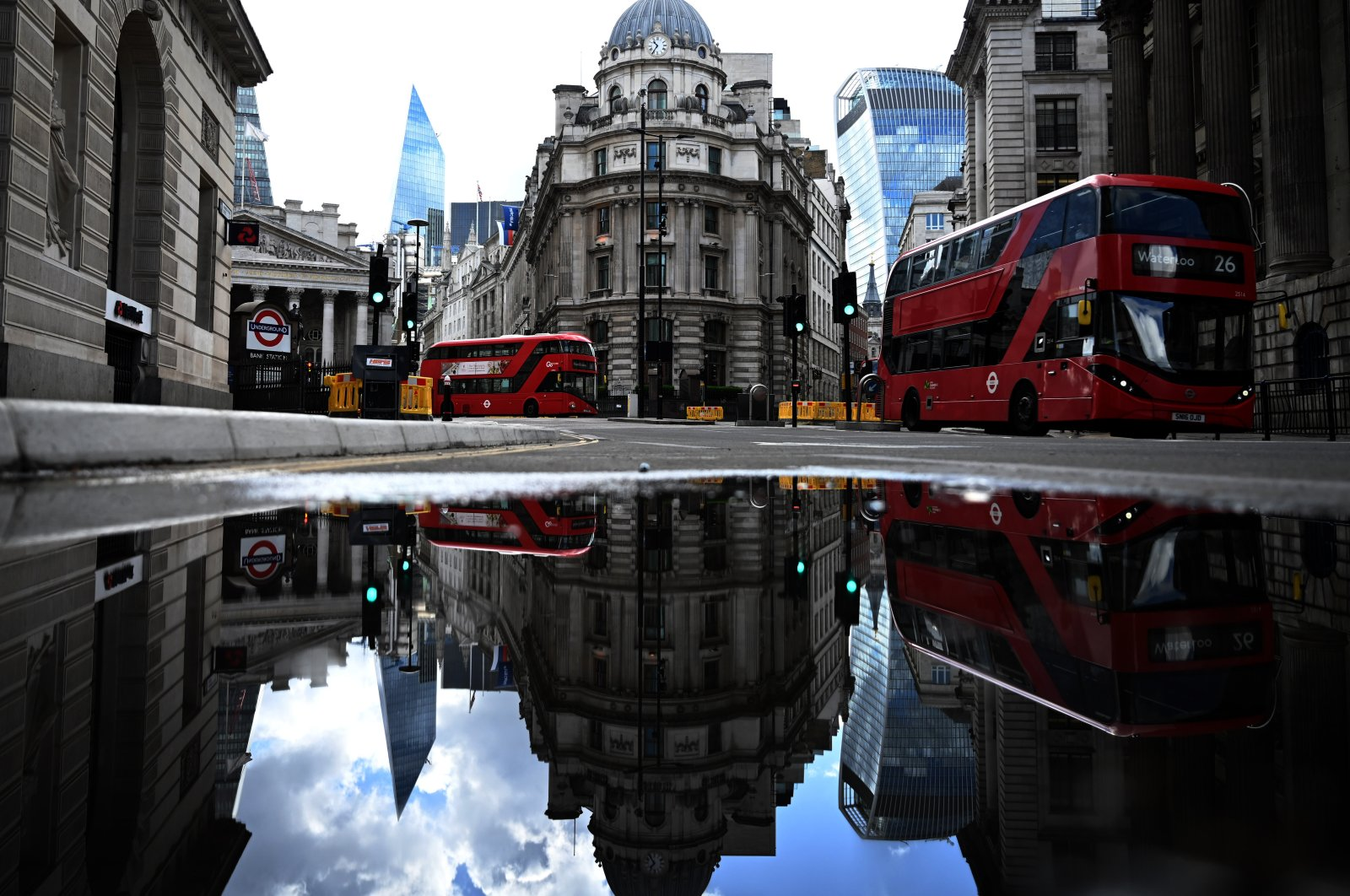 Red buses pass the Bank of England in the financial district of London, May 14, 2020. (EPA Photo)