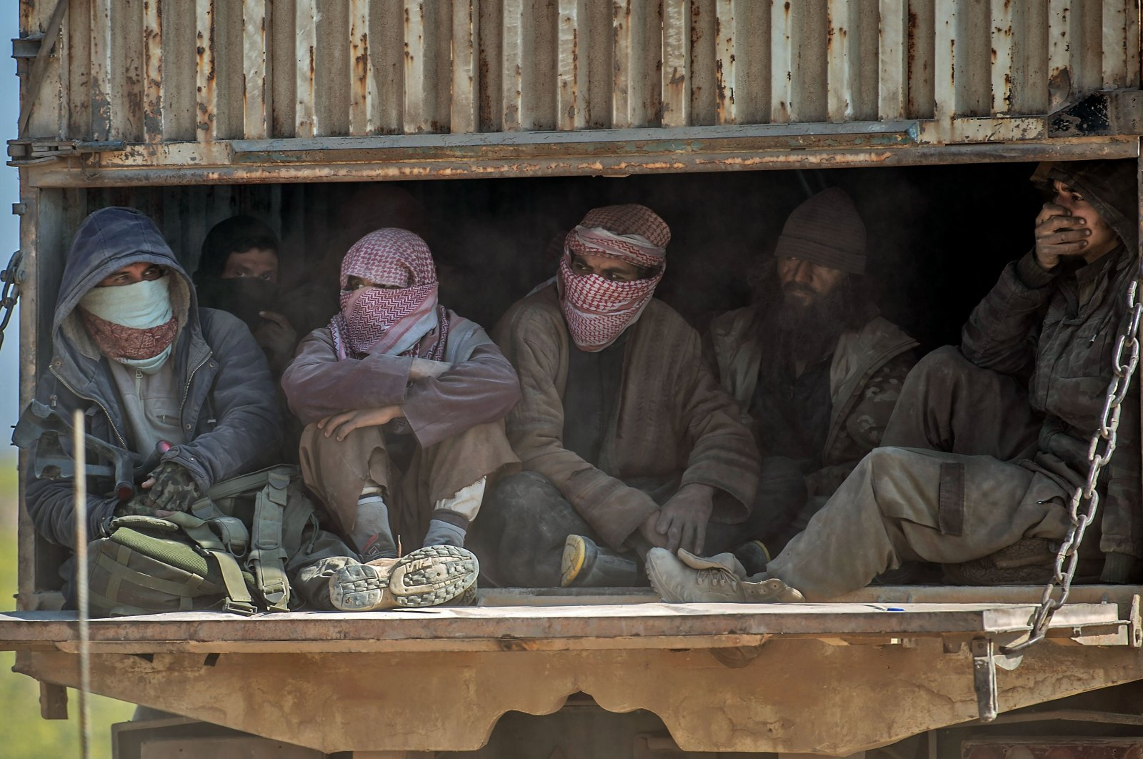 A truck carrying men, identified as Daesh members, being transported out of the terrorist organization's last holdout of Baghouz in Syria's northern Deir el-Zour province, Feb.20, 2019. (AFP)
