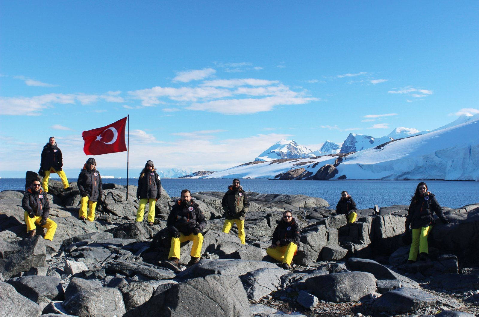 Turkish scientists pose next to a Turkish flag in this undated photo from their first Antarctica expedition in 2016. (İHA Photo)