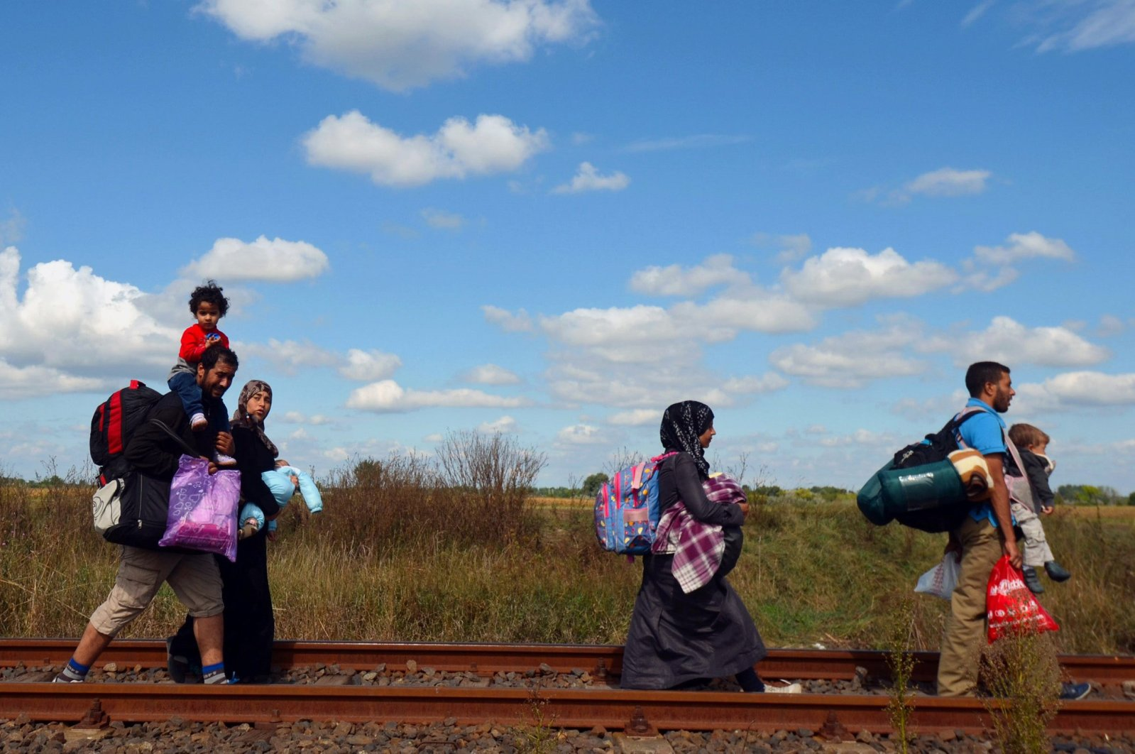 Migrant families walk on the railway track at the Hungarian-Serbian border near the village of Roszke, Hungary, Sept. 6, 2015. (AFP Photo)