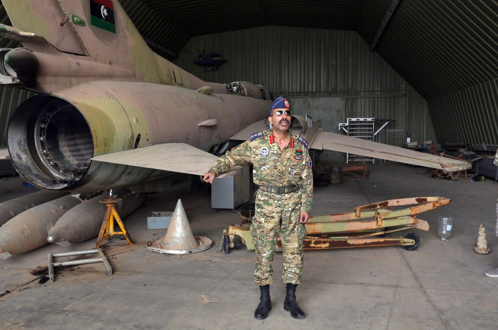 Group Capt. Muhammad Qanunu, the military spokesperson of Libya's internationally recognized government, stands by a partially disassembled MiG-23 aircraft after seizing Al-Watiya air base, southwest of the capital Tripoli, May 18, 2020. (AFP Photo)