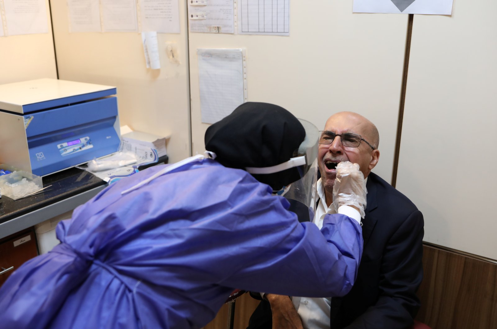 A member of the medical team wears a protective suit as she collects saliva of a man to be checked at a testing center for COVID-19, in Tehran, Iran, May 20, 2020. (WANA via Reuters)